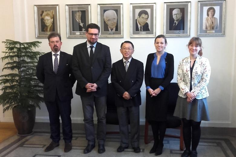 zdjęcie: pięć osób stoi za nimi widać ścianę z portretami